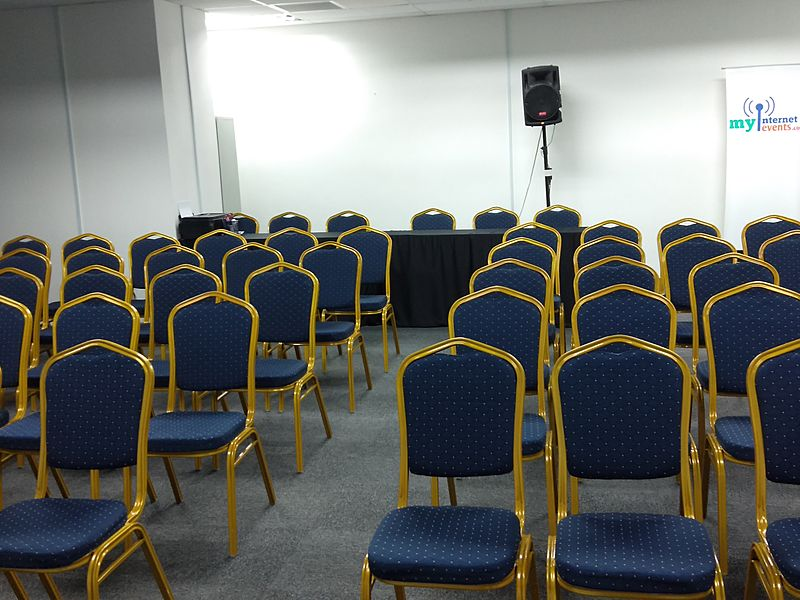 kuala lumpur event space with speaker and golden-blue chairs