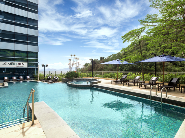 outdoor swimming pool surrounded with hotel building and trees