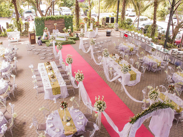 semi outdoor wedding space; red carpet leading to stage