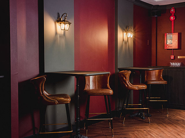room with brown bar stools and cocktail tables
