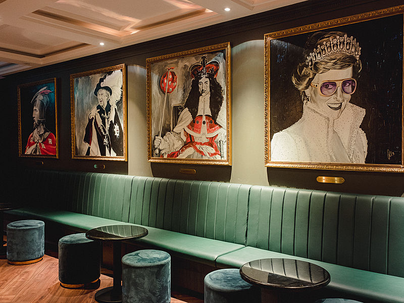 green long couch and lady diana painting in bar lounge singapore