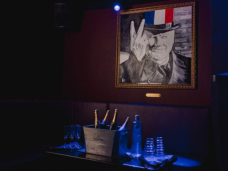 room with bottles of wine and a painting of a man with italian flag cap