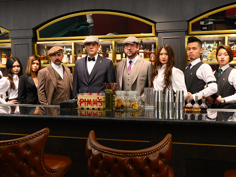 the monarchy bar singapore team standing behind the bar counter