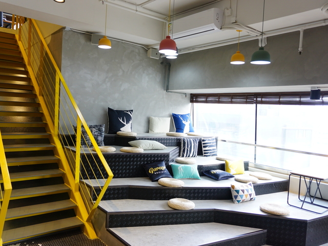 auditorium area with lot of colourful cushion and hanging lights