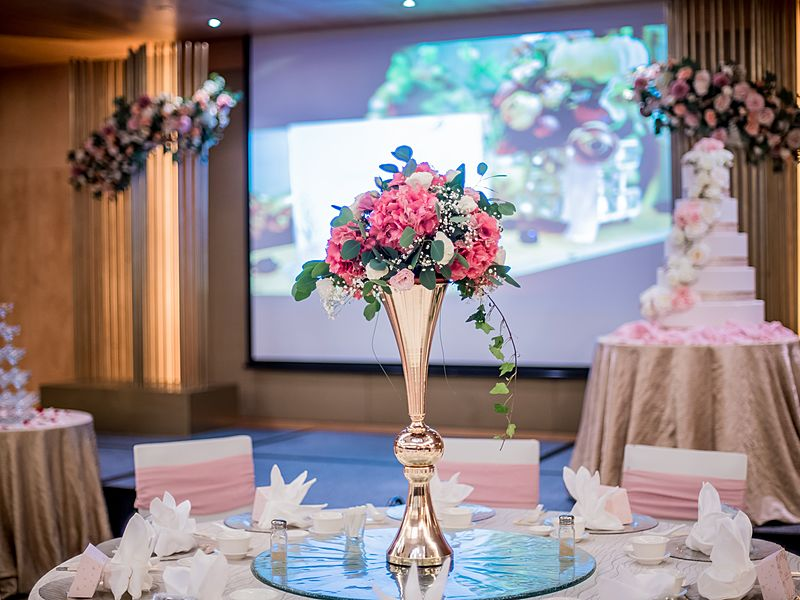 wedding party decoration with wedding cake screen projector and tree in the table