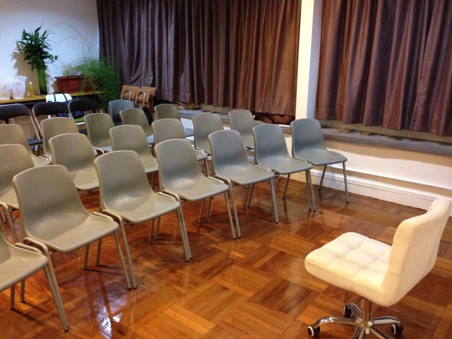 private conference room using theatre seating setup and one chair for speaker