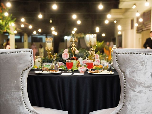 bride and groom's table decorated with flowers and black tablecloth