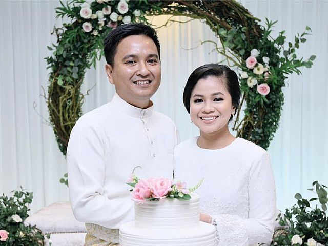 malaysian wedding couple in white taking picture together with their wedding cake