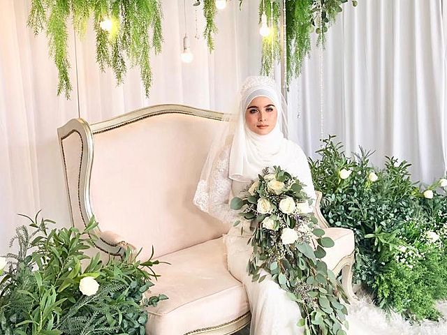 muslim bride in white gown sitting and holding a flower bouquet