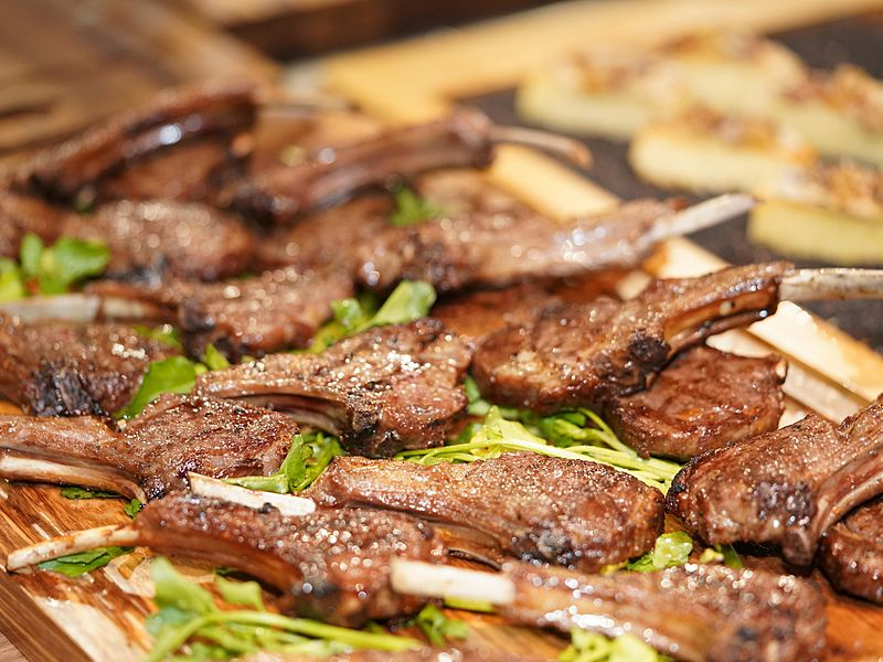 small grilled ribs served on a brown plate with a simple garnish