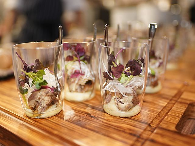 some dishes served in glass and placed on a wooden plate