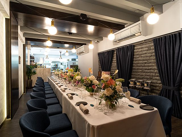 event space with long white dining table and blue chairs