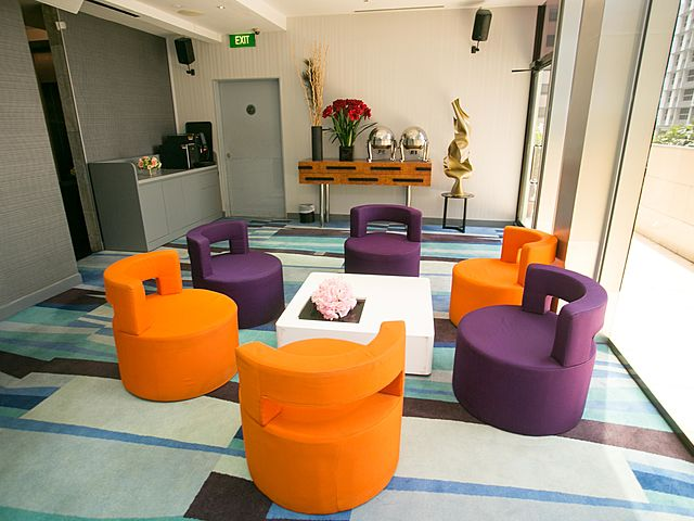 private room with colourful chairs and square white tables