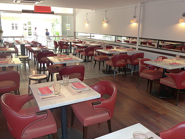 restaurant with minimalist design with red chairs and white table