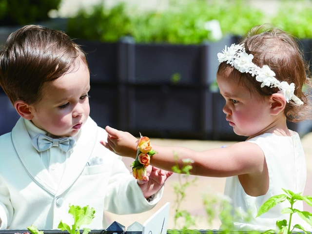 toddlers in wedding outfits playing in garden