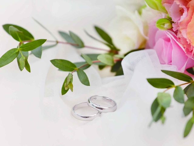 couple rings next to flower bouquet