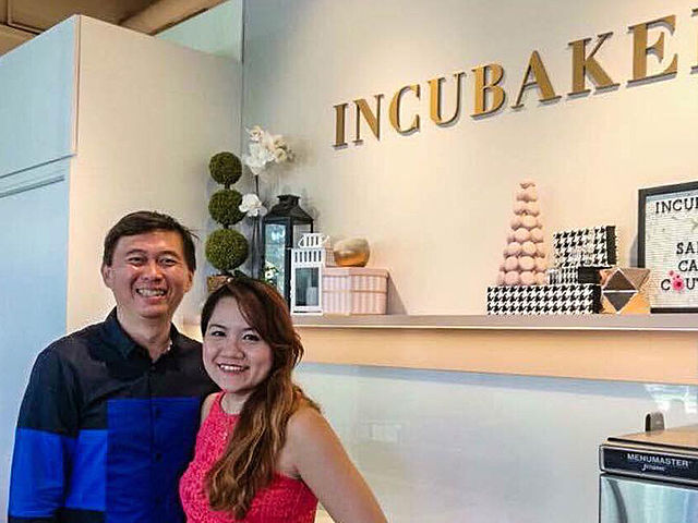 couple take a picture in front of incubaker logo