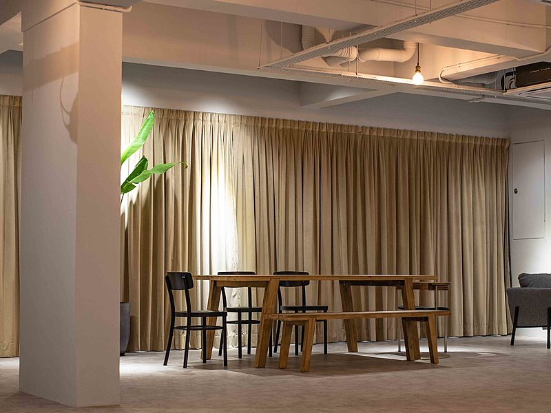 medium size function room with beige drape and wooden table