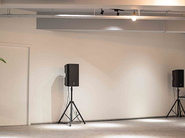 white event room facilitated with two speakers and track lighting