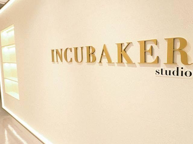 incubaker studio logo with gold colour and white wall
