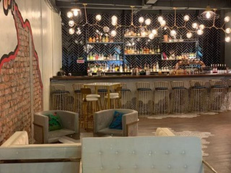 restaurant with grey minibar and several round pendant lights