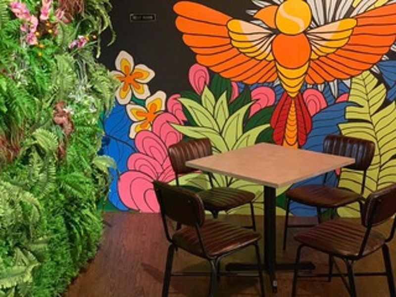 casual meeting space in penang with colourful wall painting and square table