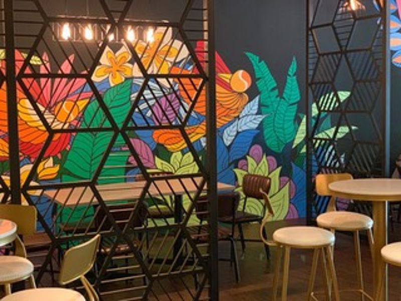restaurant dining room with colourful wall painting in penang
