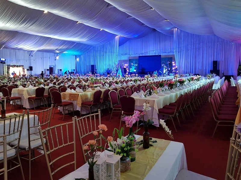 function hall with long table setup and table decoration on each table