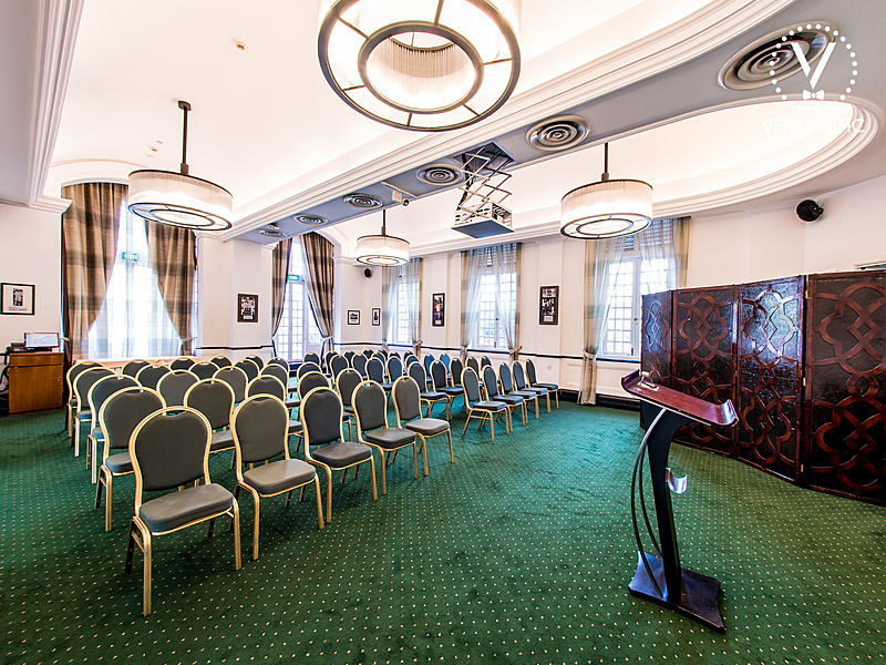 green carpet event space with speech podium and theater seating
