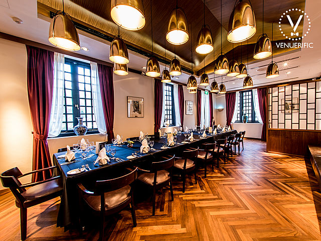 wooden floor event space with black framework window and golden pendant lamps