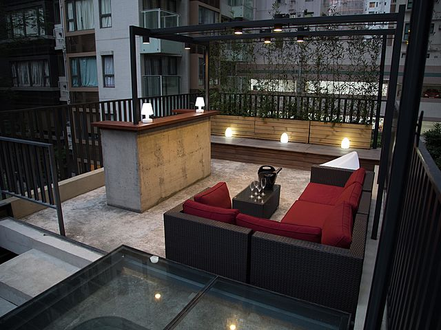 rooftop event venue with black-red long couch and several table lamps