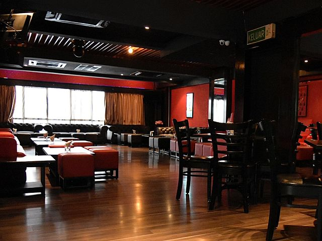 black ceiling venue with large windows and red wall
