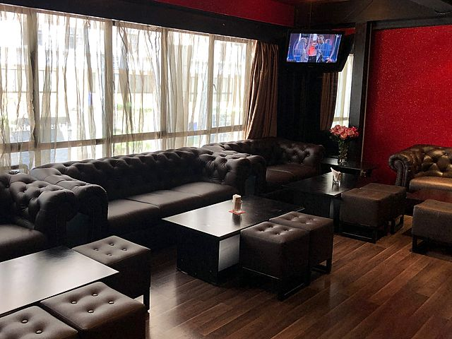 small event lounge with black couches and television