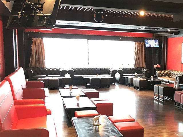 low ceiling party room in kuala lumpur with red wall and several couches