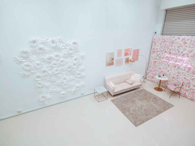 high ceiling event space in singapore with white wall and pink furniture
