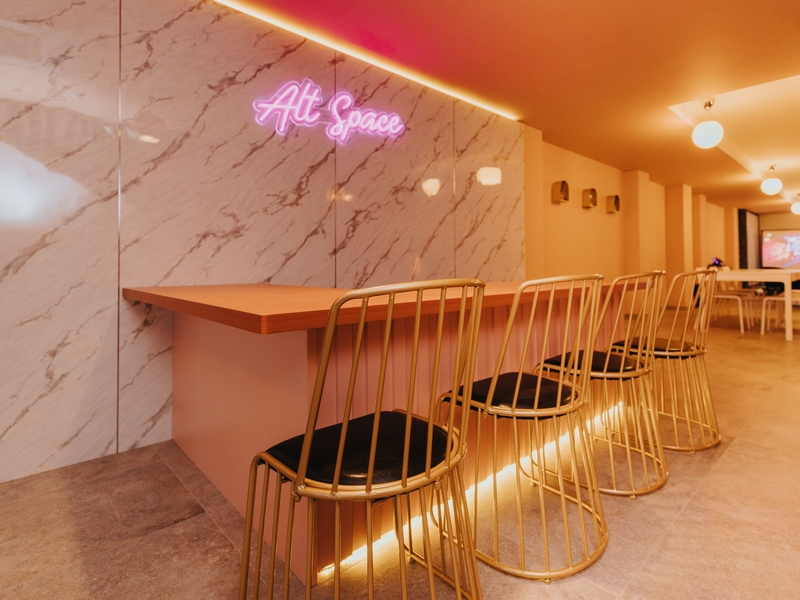 bar seating area with pink neon sign of alt space