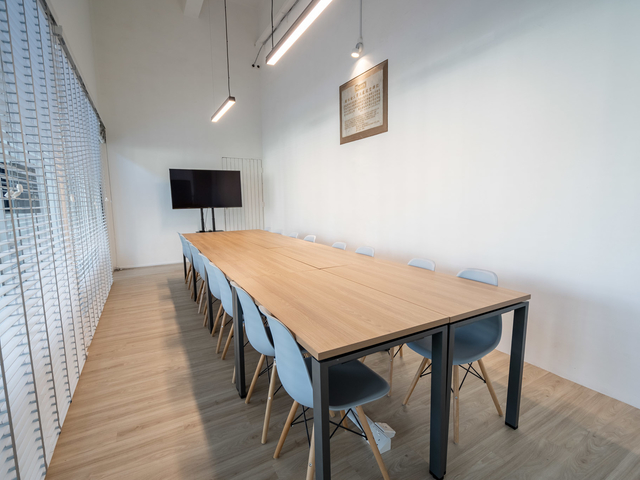 singapore private meeting space with long wooden table and tv screen