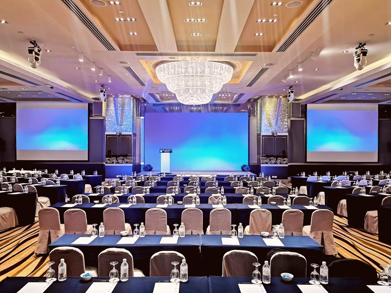 workshop event set up with long table and chair with big screen in ballrooms