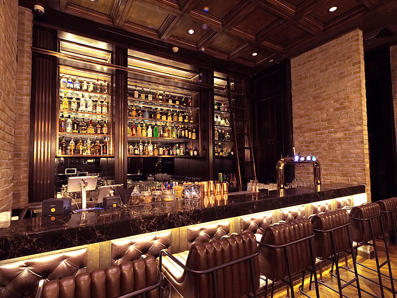 bar counter with drinks display and wooden ceiling