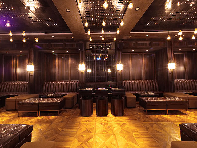 brown interior lounge in kuala lumpur with several long couches and pendant lights