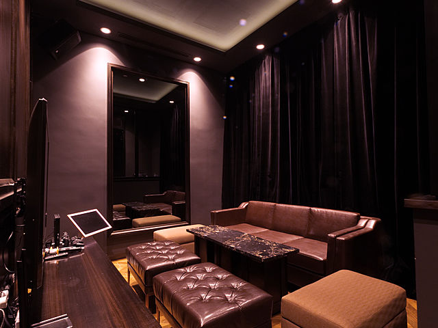 bar's mini karaoke room equipped with dark brown drape and couches