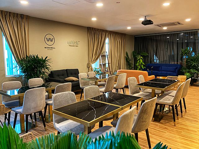 coworking space with open space with high ceiling room with four people set up table