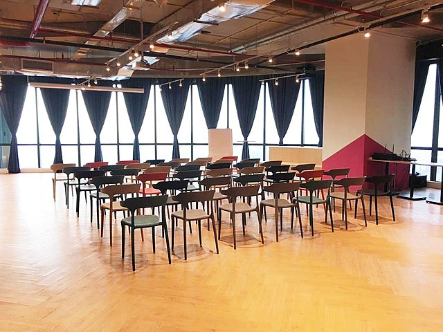 private room with natural light for 130 capacity set up with chairs for seminar
