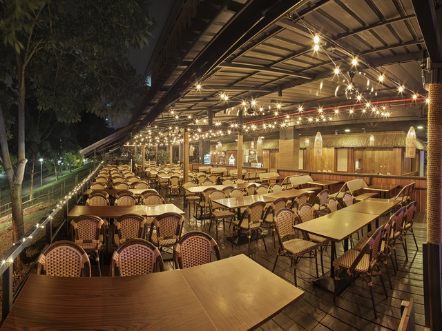 semi outdoor restaurant with wooden domination and hanging small ball lamps