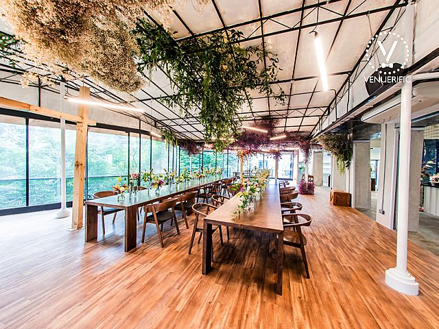 glass event space with wooden furniture and plant decoration inside