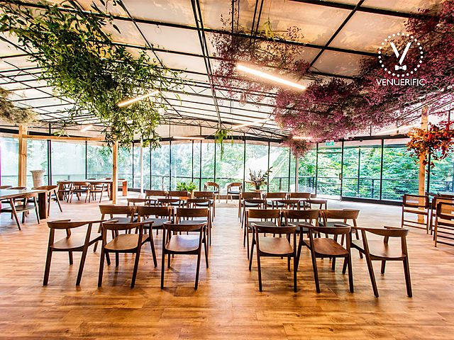 large glass venue with wooden furniture and plants decorated ceiling