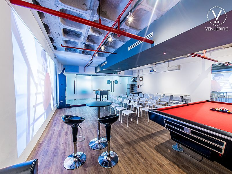 spacious seminar space facilitated with white audience chairs and a pool table