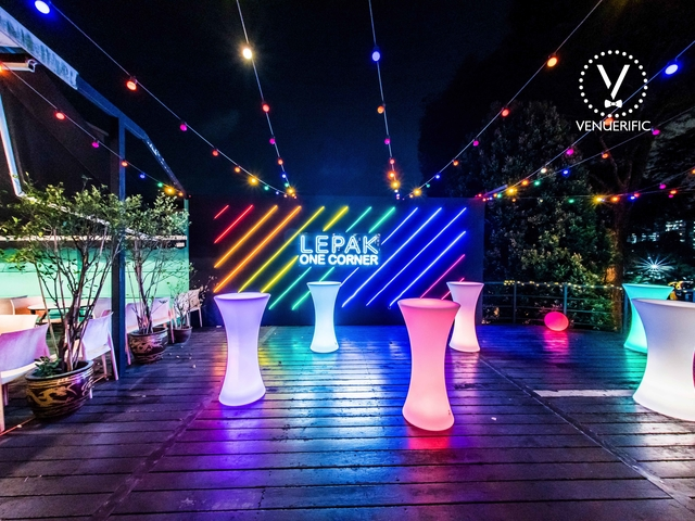 event space with colourful wall background and several cocktails tables