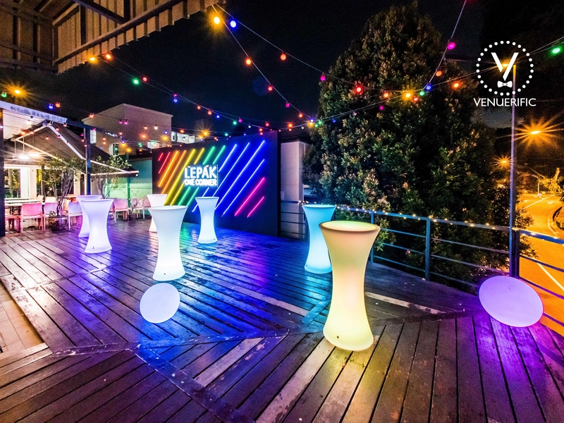 outdoor space with wooden floor and several colourful cocktail tables