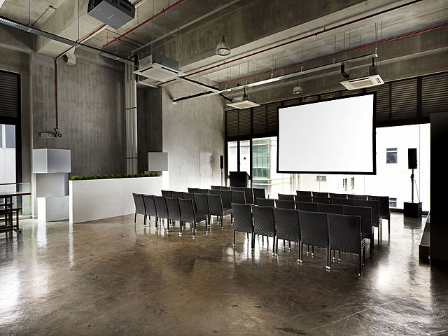 meeting space in singapore with black chairs and projector screen